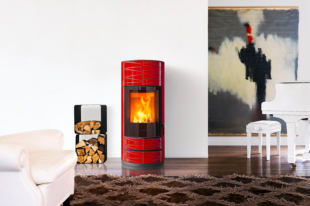 La estufa de leña ROUND M de Piazzetta llama la atención por su atrevido color rojo lava y sus refinados paneles de mayólica decorados.